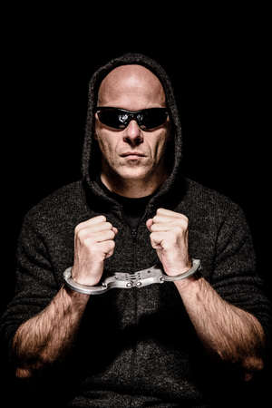 Criminal with sunglasses and hood trapped in handcuffs Stock Photo - 52650178