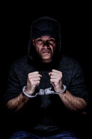 White male wearing baseball hat and hood, sit handcuffed on a chair. grunge style Stock Photo