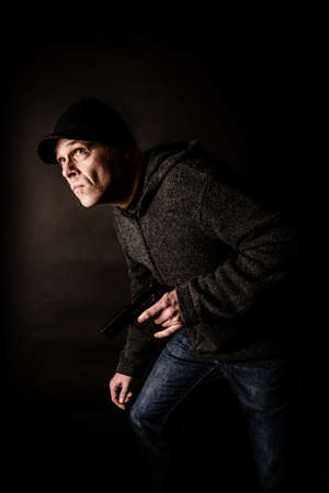 Burglar with a gun looking to break into house or office Stock Photo - 52650189