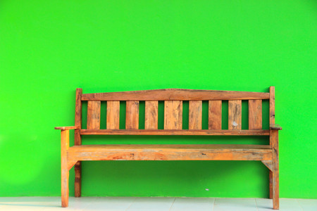 against: wooden bench against green wall Stock Photo