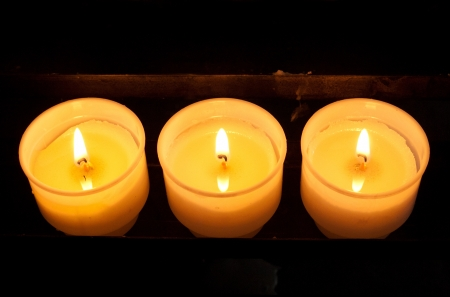 votive candle: Three prayer candles Stock Photo