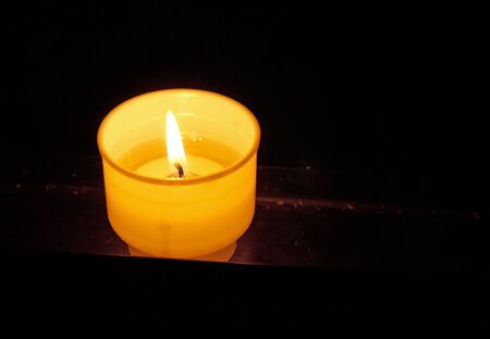 votive: Burning prayer candle in the darkness