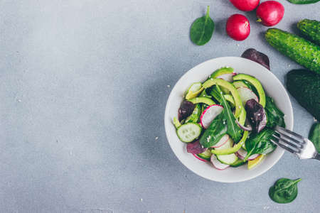 Healthy salad with radishes, avacado, cucumbers, spinach and arugula in a bowl top view