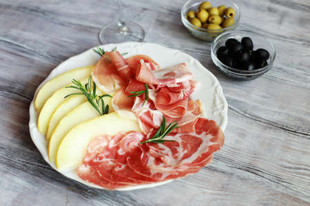 Italian appetizing snack prosciutto with melon, olives