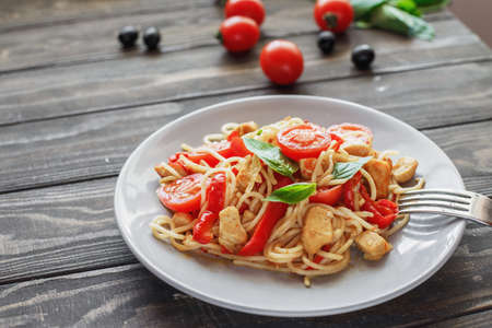 Italian pasta with chicken, tomatoes, red pepper,basil in a plate on a wooden table Stockfoto