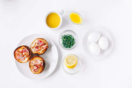 Ingredients for eggs Benedict bun with bacon, lemon, sauce, coriander Stockfoto