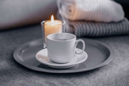 Cup of  hot coffee with a candle on a gray tray, next to a knitted gray scarf and a white sweater. Concept cozy winter home relax