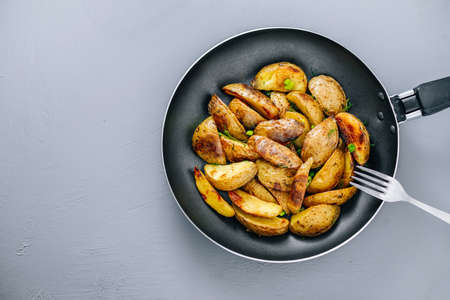 Baked potatoes in a pan on a gray background top view Banco de Imagens