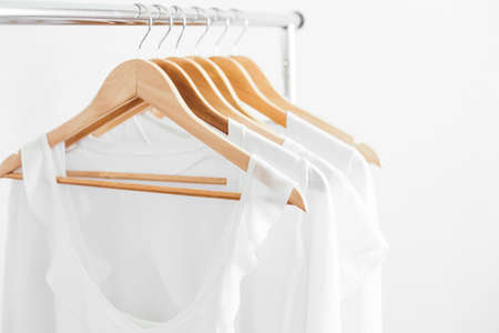 Wooden hangers with white blouses on the counter.