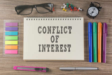 enact: Conflict Of Interest word on notebook.
