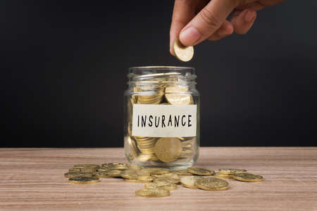 Saving money concepts, women hand putting coin in glass jar with INSURANCE word. Financial concept. Stock Photo