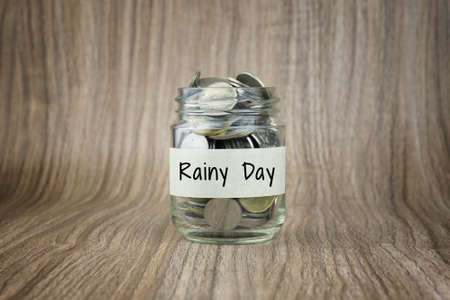 Glass jars with coins labeled Rainy Day. Financial Conceptual Stock Photo