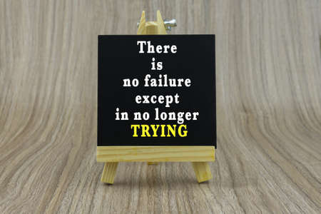 Art board, wooden easel, front view with word Inspiration quote : There is no failure except in no longer trying
