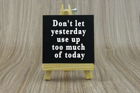 Art board, wooden easel, front view with word Inspiration quote : Dont let yesterday use up too much of today