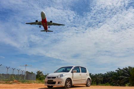 KUALA LUMPUR, MALÁSIA - 12 DE DEZEMBRO DE 2016: Aterrissagem de avião no aeroporto internacional 2 de Kuala Lumpur 2. Airasia A320-216 e o ??myvi do perodua. Foto de archivo - 73386795