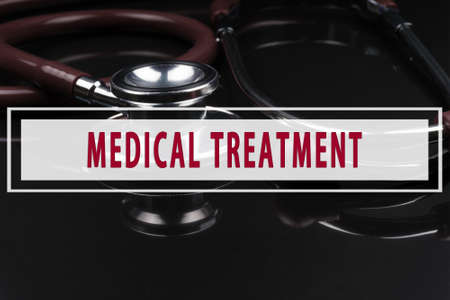 tumor stage: Stethoscope on black background with text MEDICAL TREATMENT