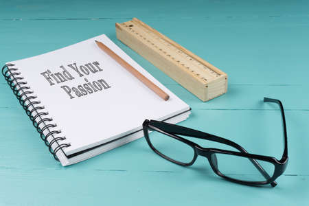 Notebook, pencil, wooden ruler, pen knife and glasses on the blue wooden background with words Find Your Passion. Top View. Business Concept.