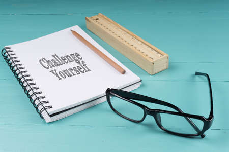 self assurance: Notebook, pencil, wooden ruler, pen knife and glasses on the blue wooden background with words Challenge Yourself. Top View. Business Concept.