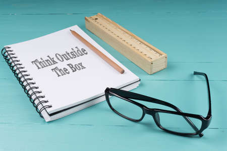 Notebook, pencil, wooden ruler and glasses on the blue wooden background with words Think Outside The Box. Top View. Business Concept.