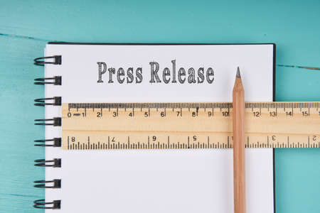 Press Release word on notebook, wooden ruler and pencil on blue wooden background. Top view. Banco de Imagens