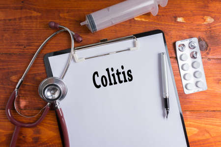 colonic: Stethoscope, syringe, pills with Colitis words on wooden background. Medical Concept.