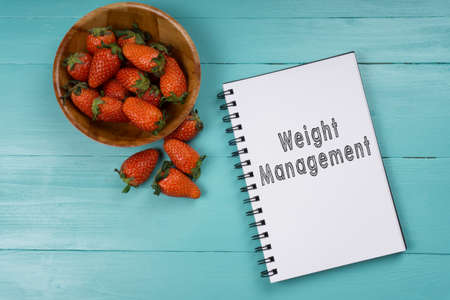 Concept image, strawberry with notebook on a blue wooden background with words Weight Management. Health concept.