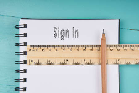 enlisting: Sign In word on notebook, wooden ruler and pencil on blue wooden background. Top view.