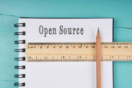 an operative: Open Source word on notebook, wooden ruler and pencil on blue wooden background. Top view. Stock Photo