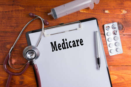 eligible: Stethoscope, syringe, pills with Medicare words on wooden background. Medical Concept. Stock Photo