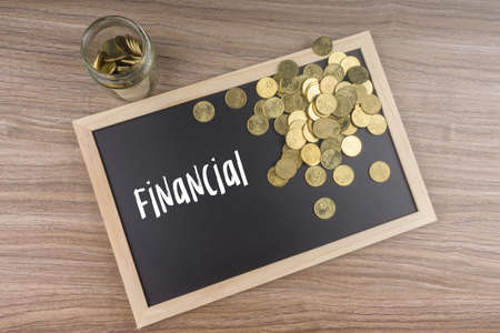 Gold coins in glass jar with Financial words on chalkboard. Financial concept.