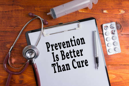 Estetoscopio, jeringa, píldoras con prevención es mejor que las palabras de curación sobre fondo de madera. Concepto Médico.