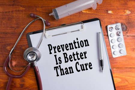 Stethoskop, Spritze, Pillen mit Prävention ist besser als Heilungswörter auf hölzernem Hintergrund. Medizinisches Konzept.