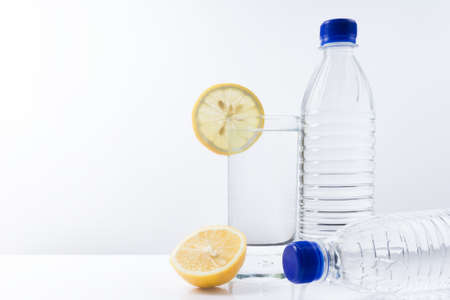 Mineral water glass with lemon and two plastic water bottles on a white background.