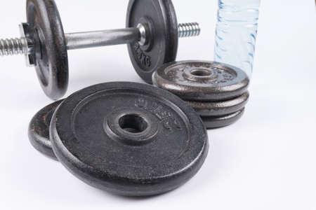 Equipo de la aptitud: pesas de gimnasia y botella de agua de entrenamiento aisladas en el fondo blanco. Foto de archivo - 82762336