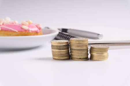 Moneda apilada con el cuaderno y el buñuelo en el fondo blanco. Concepto de negocio y financiero. Foto de archivo - 82762353