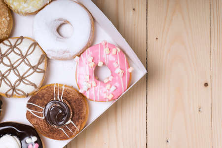Assorted donuts in a box on wooden background.