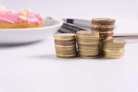 Moneda apilada con el cuaderno y el buñuelo en el fondo blanco. Concepto de negocio y financiero. Foto de archivo - 82762368