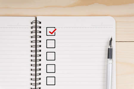 Notepad with blank checklist with fountain pen on wooden table. Stock Photo