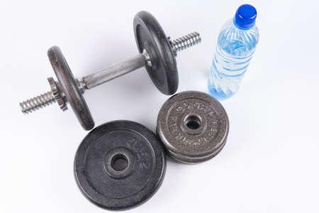Equipo de la aptitud: pesas de gimnasia y botella de agua de entrenamiento aisladas en el fondo blanco. Foto de archivo - 82762389
