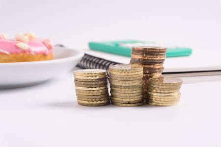 Moneda apilada con el cuaderno, el buñuelo y la calculadora en el fondo blanco. Concepto de negocio y financiero. Foto de archivo - 82762392