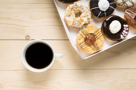 Cup with coffee and donuts on a wooden background.