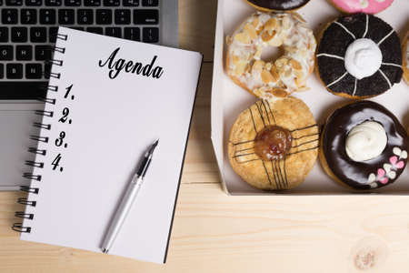 Laptop, pen, donuts and notebook written with Agenda word on wooden table, business concept. Stock Photo