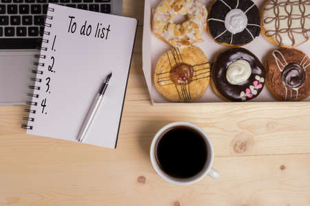 Laptop, pen, coffee, donuts and notebook written with To do list word on wooden table, business concept. Stock Photo