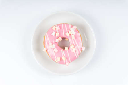 Donut covered with pink icing on white background. Stock Photo