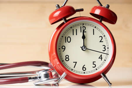 Red alarm clock and stethoscope on wood table. Doctors desk.