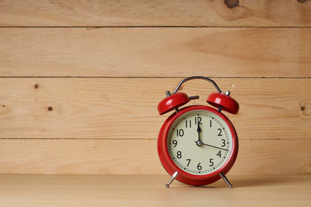 Old red alarm clock, Red alarm clock shows to 12 o'clock on wood table with wooden background. Stock Photo