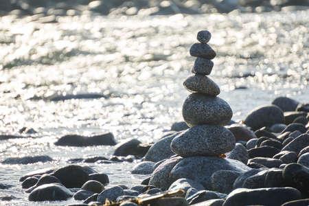 Stack of pebble stones over bokeh background. Concept zen, spa, summer, relax.