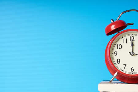 Red alarm clock on blue background with copy space.