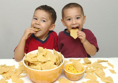 snack: Two preschool brothers enjoy chips and queso Stock Photo