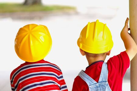 viewed: Two boys wearing hard hats viewed from behind